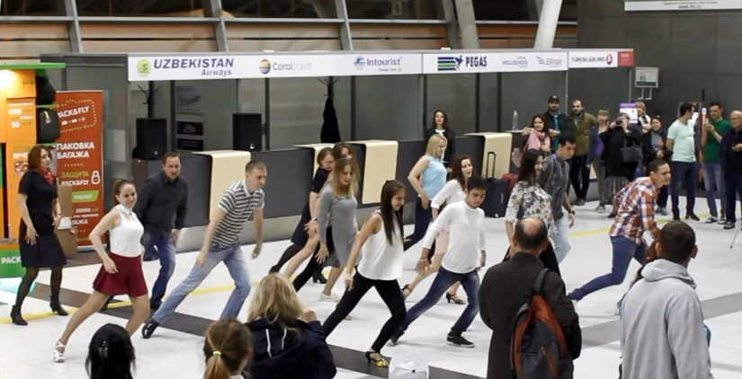 Dances out of the blue at Kazan airport during check-in for the flight to Prague